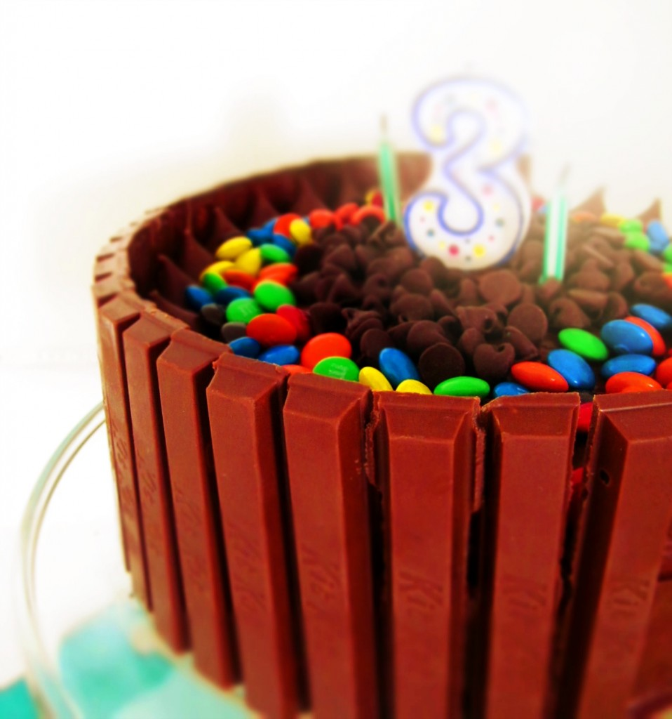 Kit Kat Birthday Cake - lined with candy bars, this birthday cake is topped with M&M candy and semi-sweet chocolate chips.