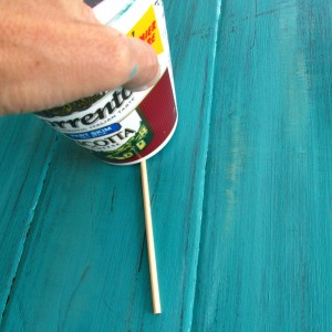 Weather your wood while the paint is still damp. Here, I used a wooden skewer and pressed it in by rubbing it with a plastic cup. This left a visual line, but also a slight indent.